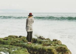 A Woman Standing Next to a Body of Water