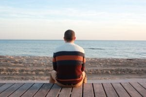 A Man is Sitting in front of Beach
