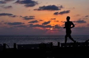 man running and exercising on the beach at sunset