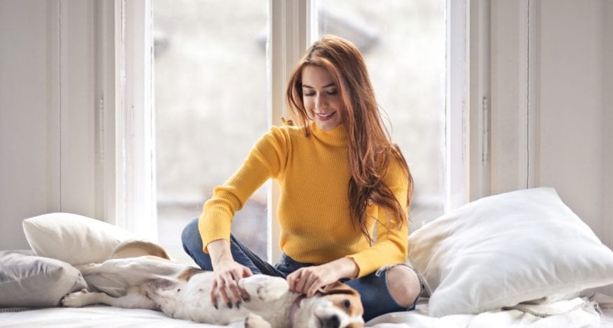 Woman petting a dog on bed
