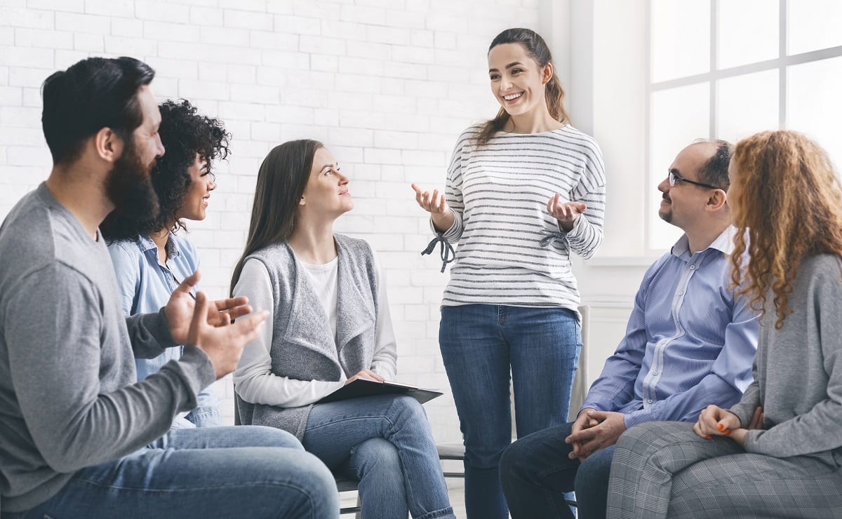 Woman sharing her progres with group on therapy session in rehab