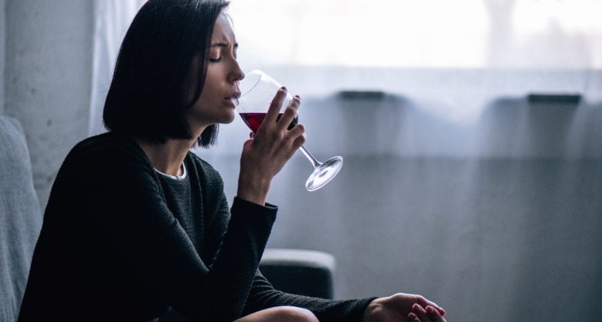 depressed woman sitting on couch and drinking wine