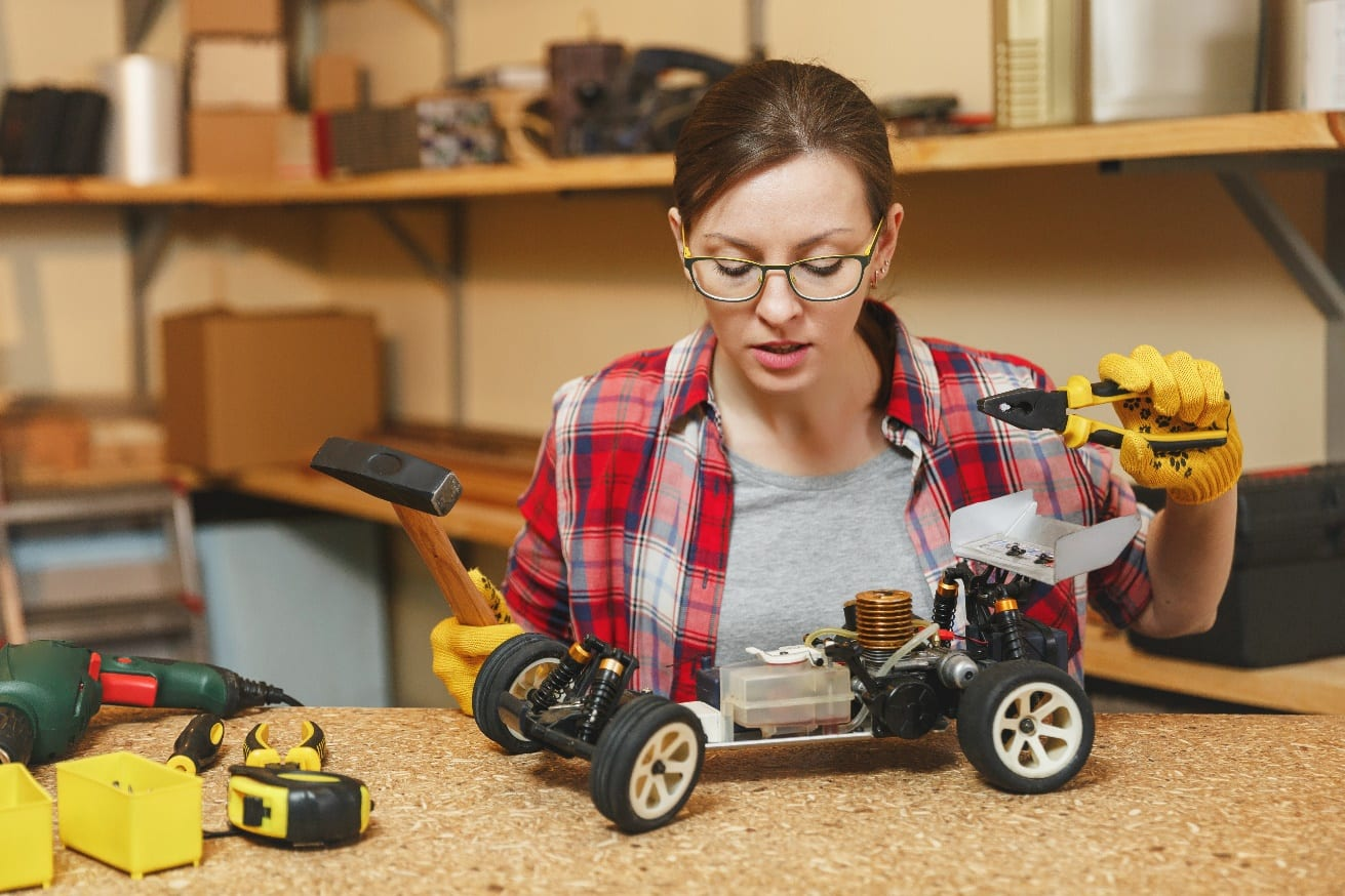 Beautiful young woman yellow gloves making toy car iron model constructor