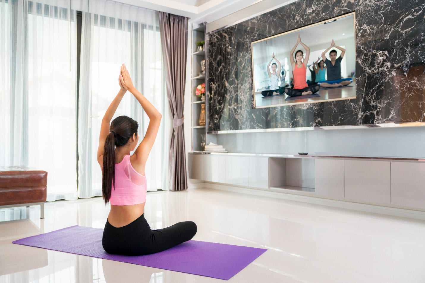 Asian lady training Yoga by follow coach in television in living room