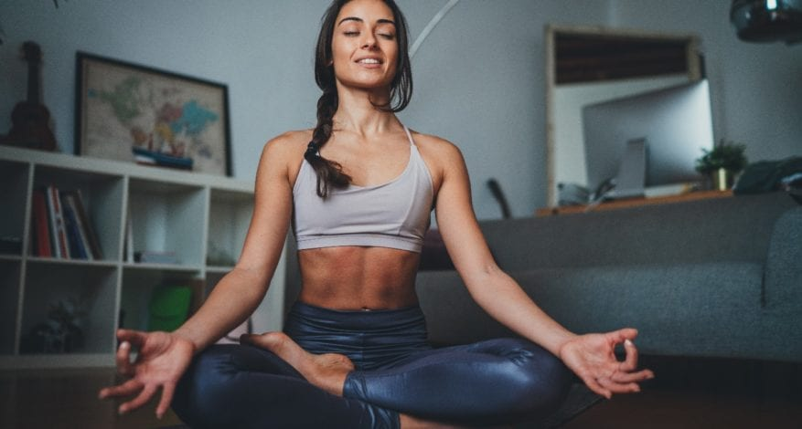 young sportive woman meditating at home in the morning practicing yoga