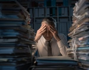 Desperate businessman in office overloaded with work, his desktop is covered with paperwork