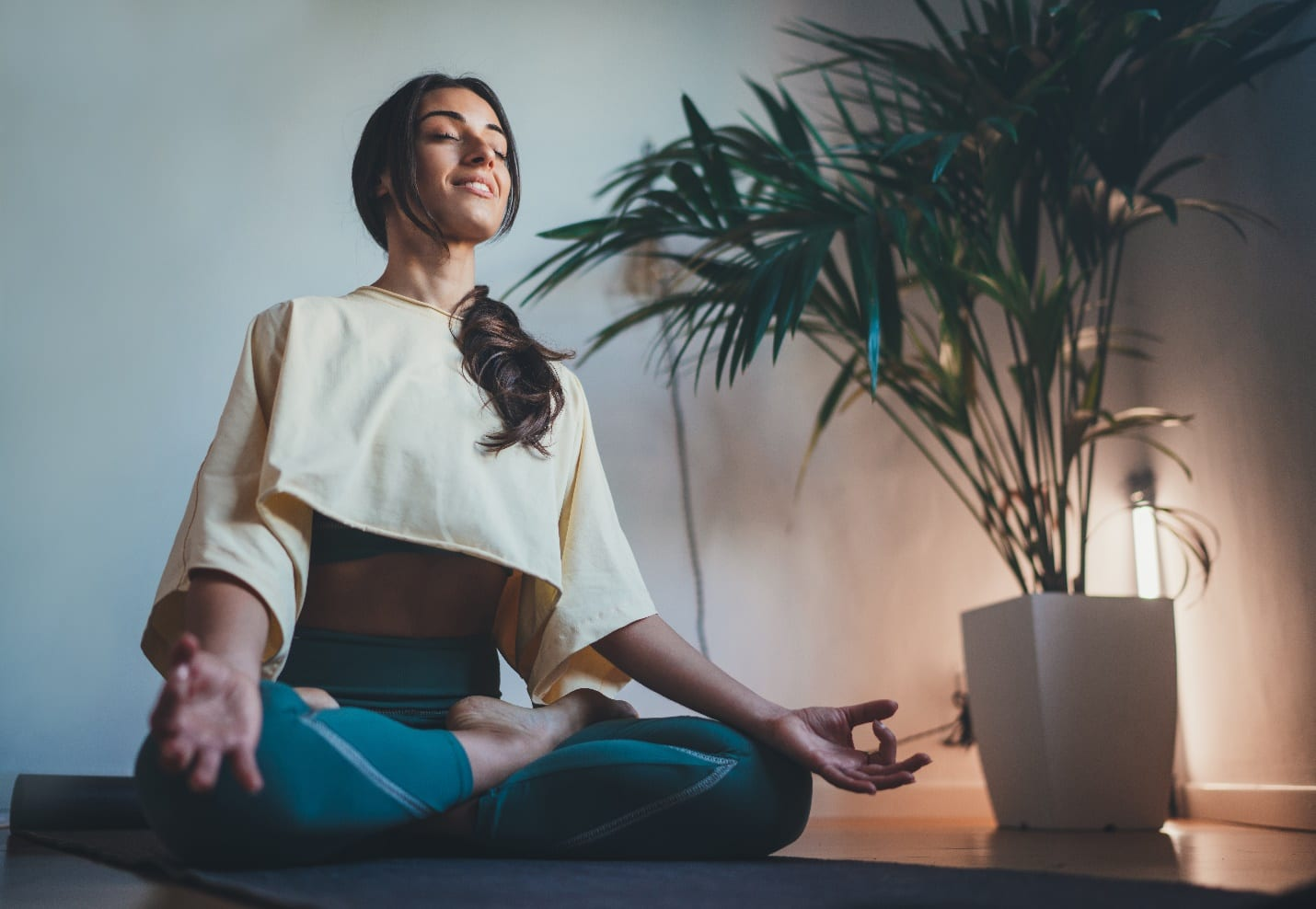 Young happy beautiful woman practicing yoga at home sitting in lotus pose
