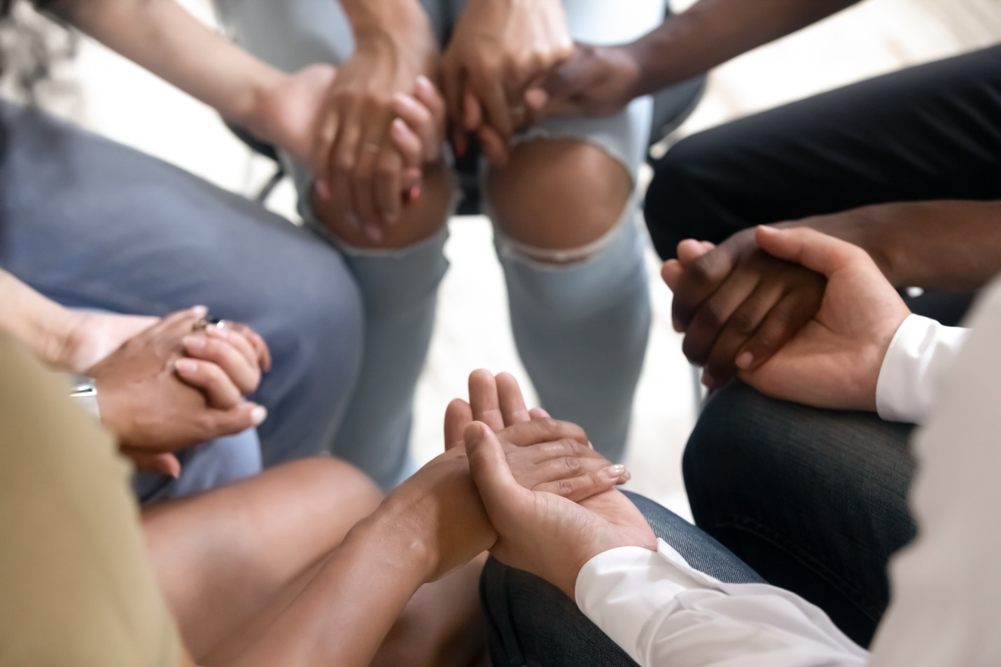 Diverse people sitting in circle holding hands at group therapy session