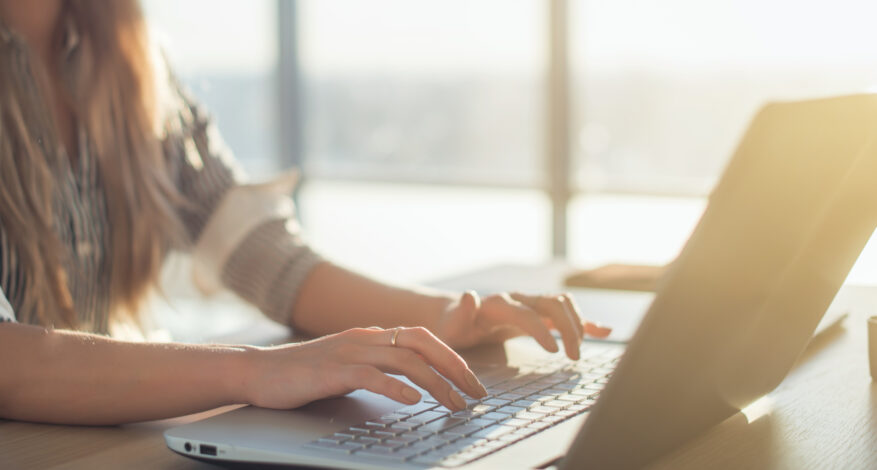 Female writer typing using laptop keyboard at her workplace in the morning. Woman writing blogs online, side view close-up picture.