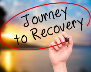 Residential Program Man Hand writing Journey to Recovery with black marker on visual
